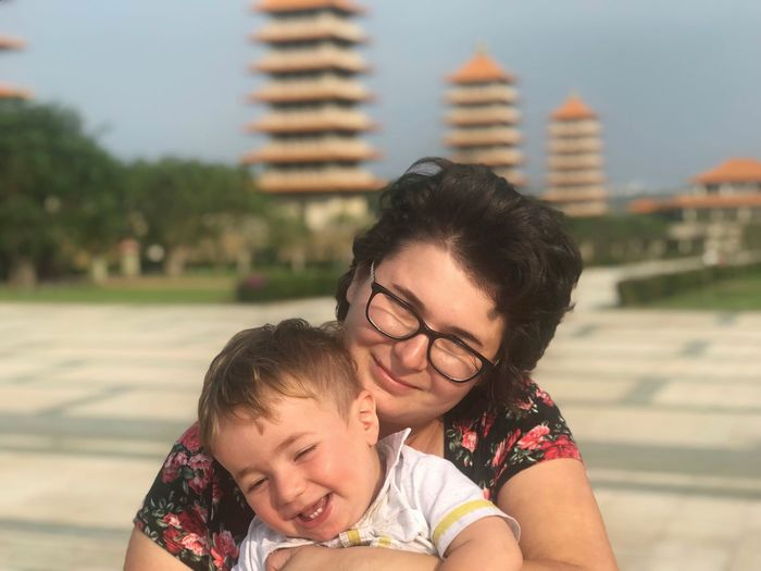 Close-up of mother with cheerful son against stupas
