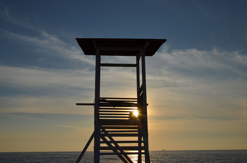 Lifeguard hut by sea against sky during sunset