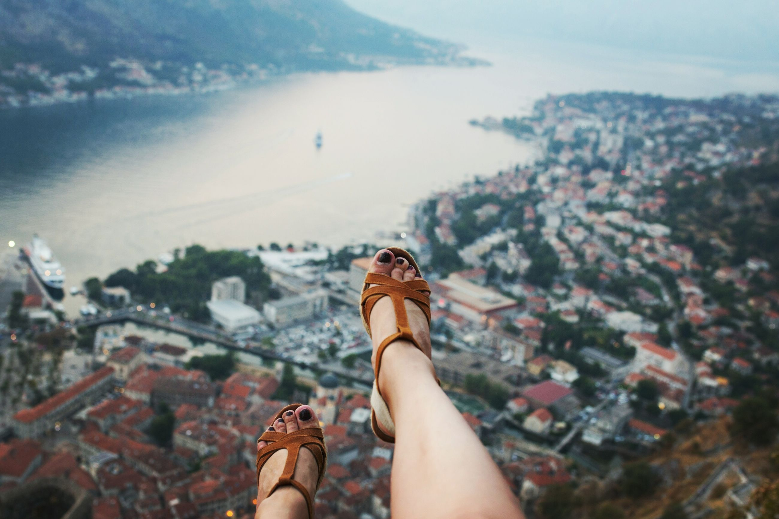 personal perspective, human body part, architecture, leisure activity, one person, lifestyles, real people, body part, nature, building exterior, sky, built structure, day, adult, city, focus on foreground, women, mountain, cityscape, outdoors, human foot