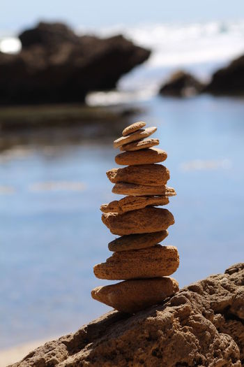 Close-Up Of Stones Stacked On Rock By River