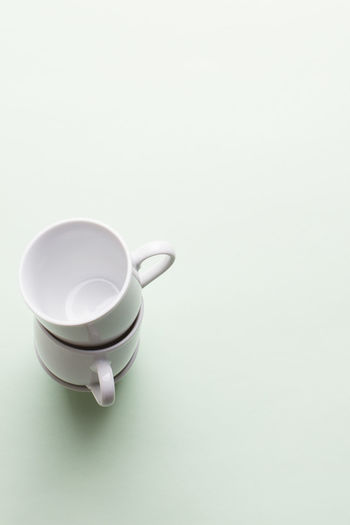 cups stacked on light green background Coffee Coffee Cup Copy Space Crockery Cup Drink Food And Drink Freshness High Angle View Indoors  Kitchen Utensil Mug No People Non-alcoholic Beverage Refreshment Still Life Studio Shot Tea Tea Cup White Background White Color