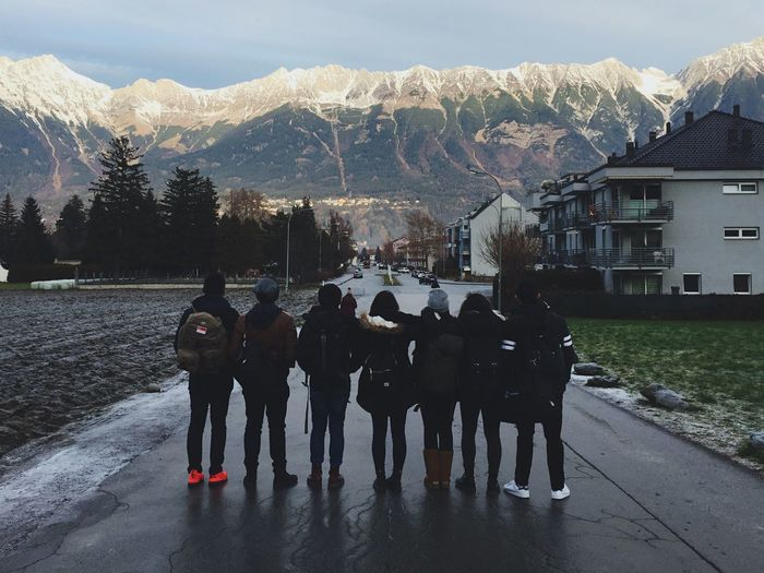 Full Length Rear View Of Friends Standing On Wet Road Against Mountains