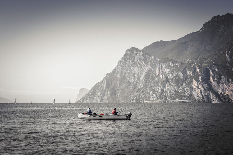 People Fishing In Sea By Mountains Against Sky