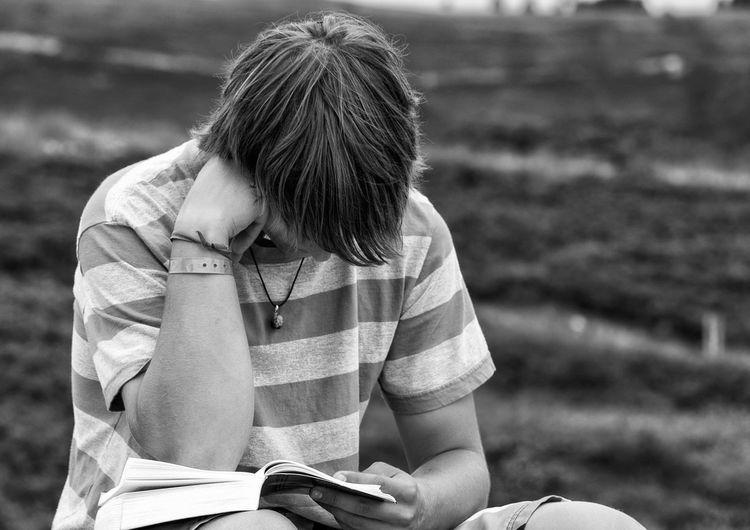 Teenage boy studying on field