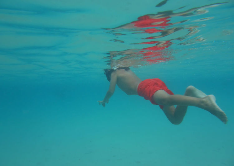 Boy swimming at sea Reflection Sea Water Nature Real People Boy Swimming Blue Travel Kid Underwater Liquid Surface Activity Swim Tropical Dive Transparent Aquatic UnderSea Lifestyles Human Body One Person Underwater Diving Swimwear Outdoors