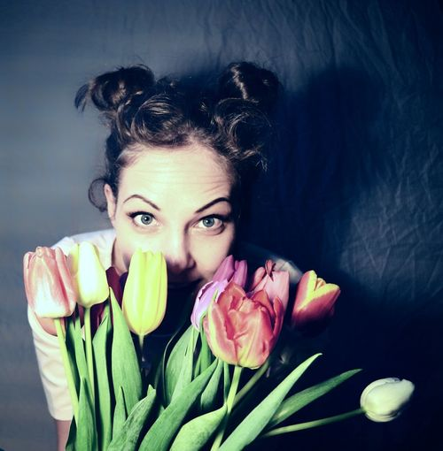 High angle portrait of young woman with colorful tulips by wall