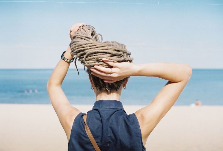 Rear View Of Woman Holding Dreadlocks At Beach