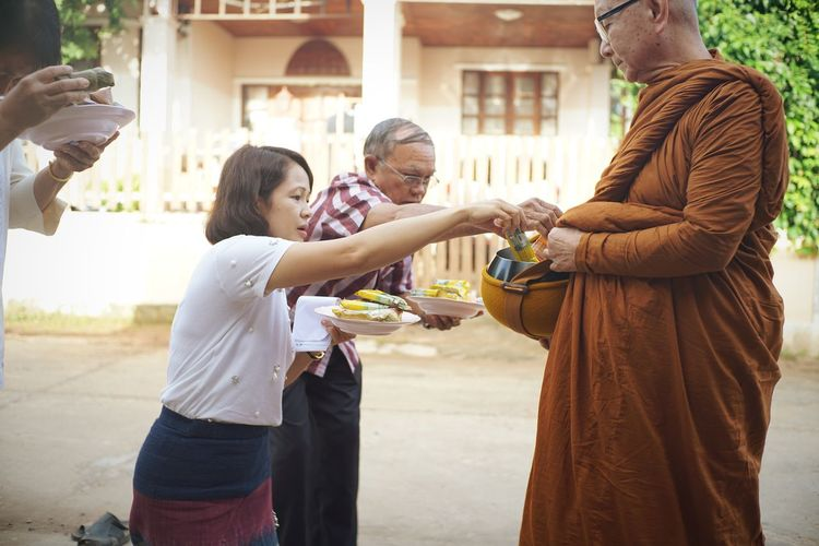 Father and daughter giving food to monk on road