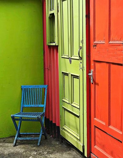 Empty chair against closed door of building