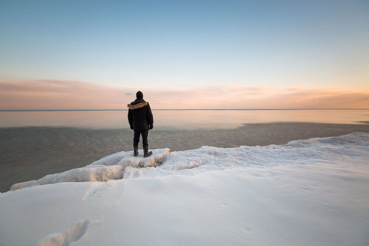 Rear view of man looking at sea while standing on snow during sunset