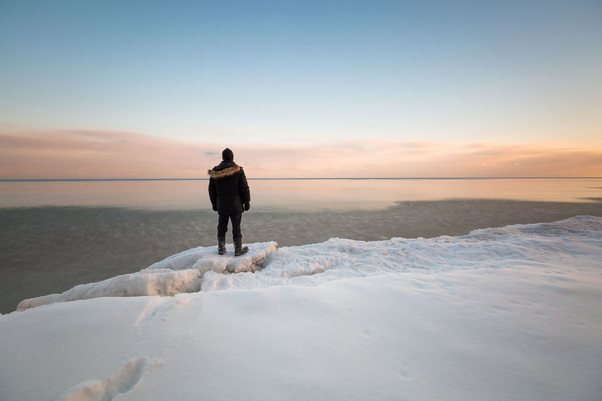 winter calm Winter Sunset Ice Snow Cold Temperature Cold person Man Lone Person Lakeshore Water Clear Sky Full Length Sea Low Tide Sunset Beach Blue Standing Rear View Seascape Dramatic Landscape Coast Weather Condition Frozen Icicle Coastal Feature