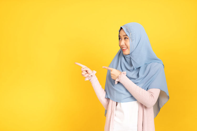 Full length of a smiling young woman against yellow background