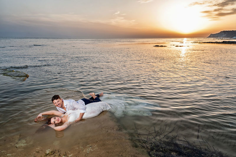 Beauty In Nature Couple - Relationship Heterosexual Couple Horizon Horizon Over Water Idyllic Land Leisure Activity Men Nature Outdoors Positive Emotion Relaxation Scenics - Nature Sea Sky Sun Sunset Togetherness Trip Two People Vacations Water