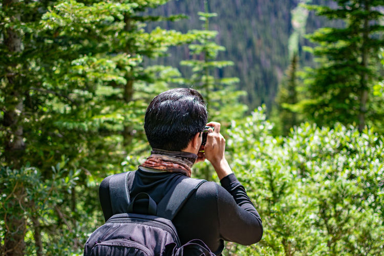 Rear view of man photographing in forest against mountains