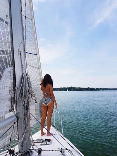 Rear view of woman wearing bikini standing on sailboat in sea against sky