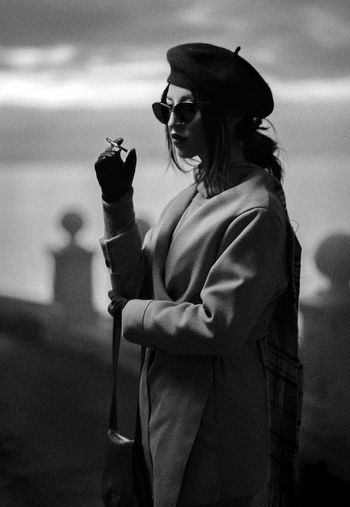 Woman Holding Cigarette While Standing Outdoors