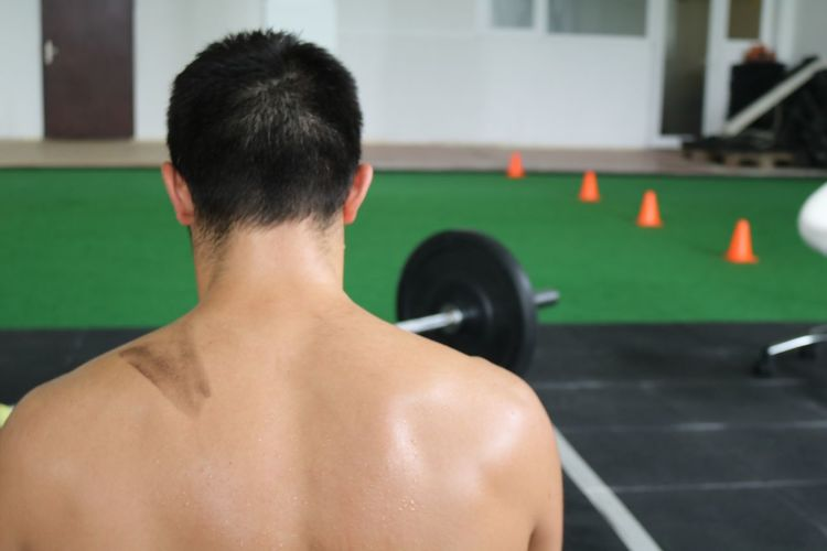 Rear View Of Shirtless Man In Gym