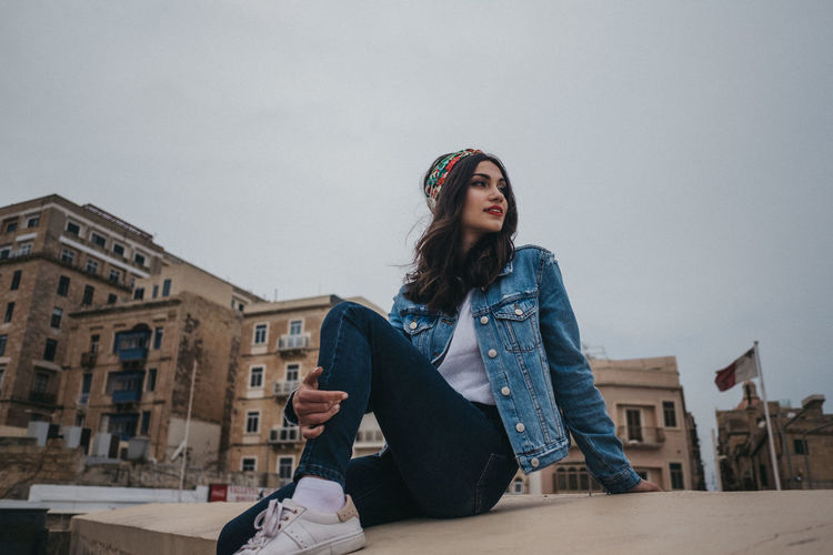 Portrait of beautiful young woman sitting against sky