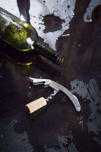 Close-Up Of Bottle And Corkscrew On Table