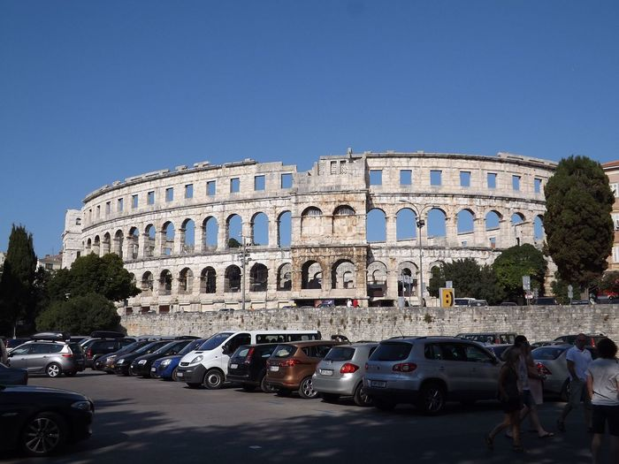 Cars parked by pula arena against clear blue sky