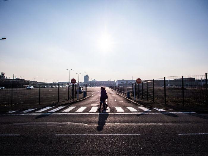 People walking on zebra crossing against clear sky