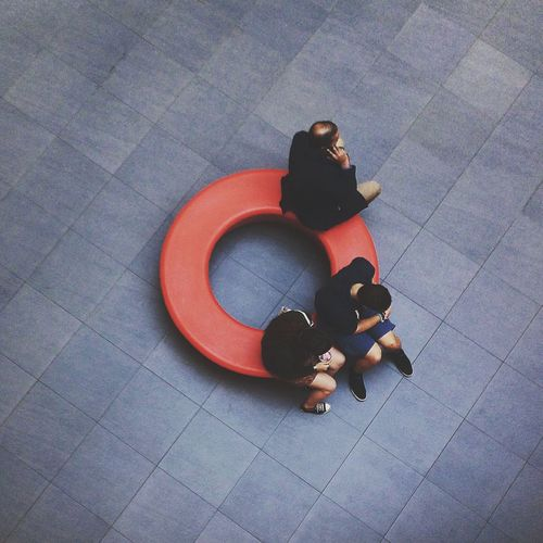 High Angle View Of People Sitting On Circular Seat In Lobby