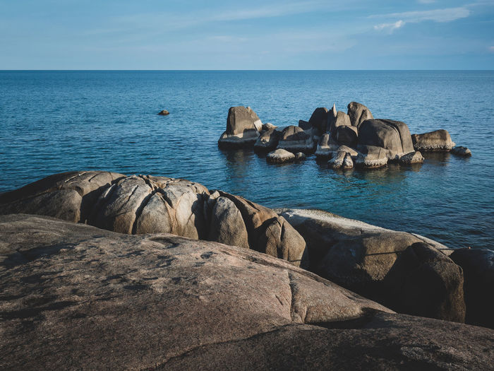 Scenic view of rock formation bay with blue water against sky. hin ta hin yai, koh samui, thailand.