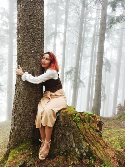 Full length portrait of woman standing by tree trunk in forest