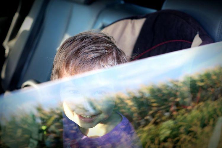 Portrait of cute smiling girl sitting in car