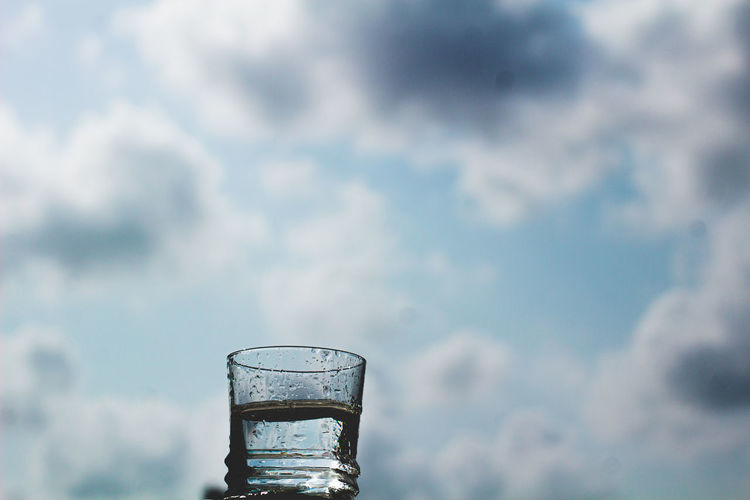 Close-up of glass of water against cloudy sky