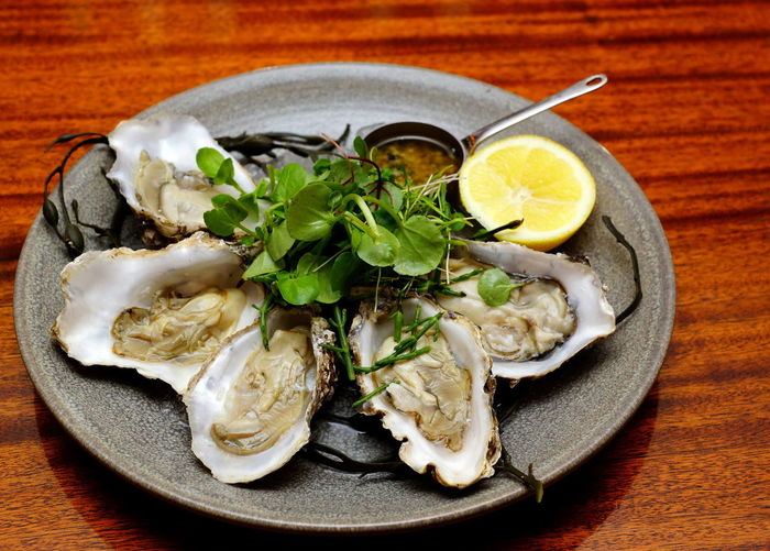 High angle view of oysters served on wooden table