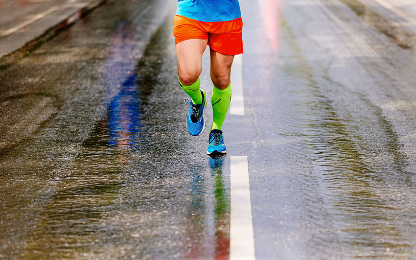 Low section of man running on wet street