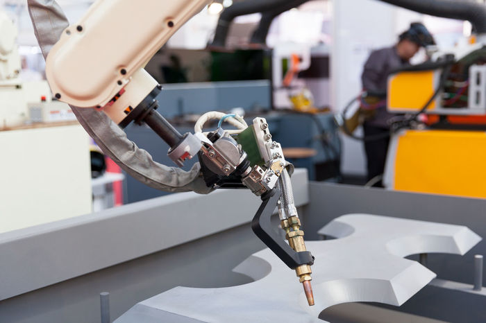 Industrial welding robot arm in the focus, blurred welder in the background Industry Industrial Machine Welding Worker Automated Automatic Automation Engineering Factory Industrial Robot Manufacture Manufacturing Metal Operating Robot Robotic Arm Steel Technology Tool Welder