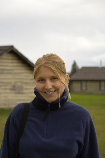 young woman in a rural scenery - with a smile Blond Hair Building Exterior Built Structure Casual Clothing Close-up Farm Fleece Front View Happiness Happy Head And Shoulders House Looking At Camera One Woman Only One Young Woman Only Outdoors Portrait Real People Rural Scene Smile Smiling Woman Portrait Wood - Material Young Woman Young Women