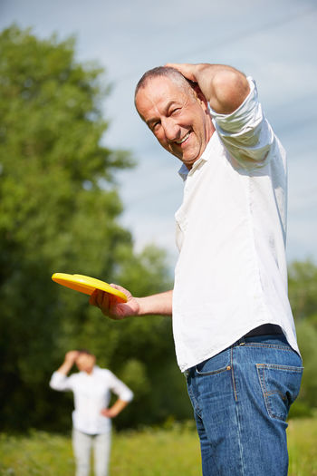 Portrait Of Smiling Senior Man Holding Plastic Disc While Playing With Woman In Park
