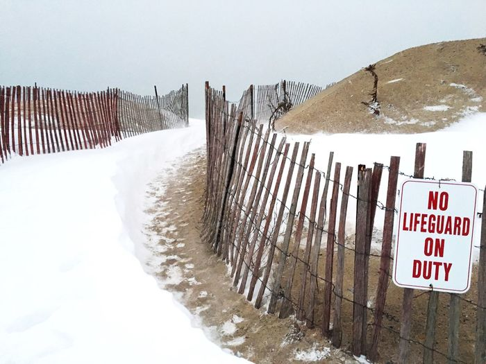 Information sign on fence against sky