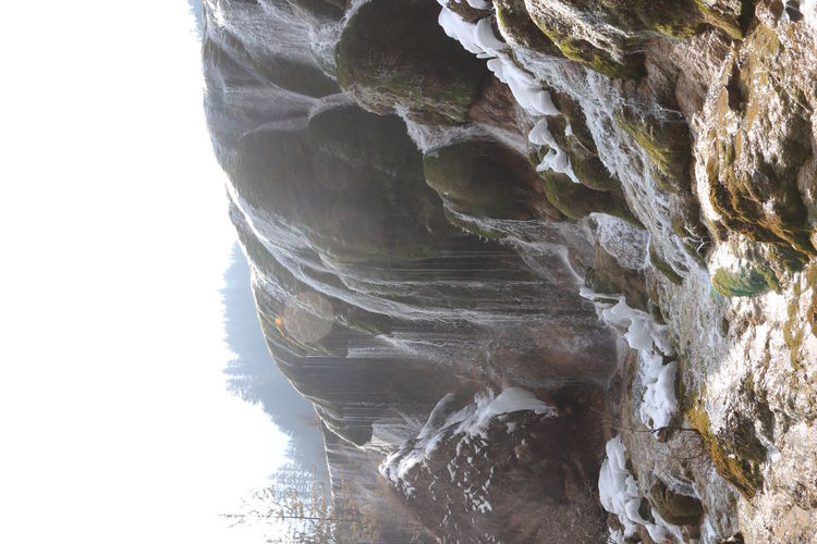 Close-up of rock formation against waterfall