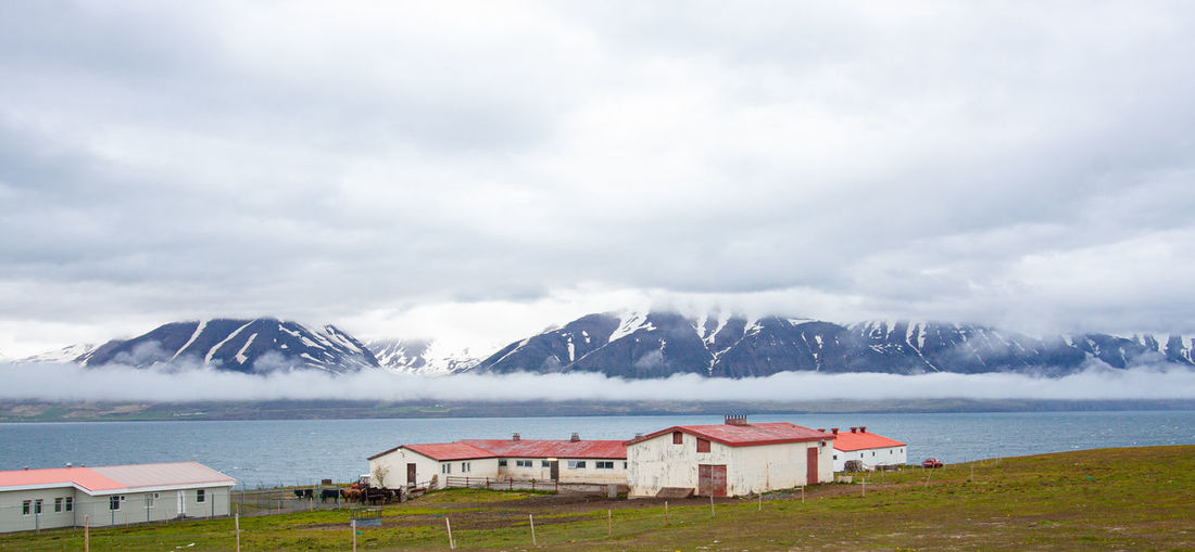 View from icelandic island back to misty mountains on the mainland. small houses in the foreground.