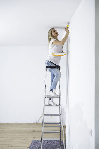 Young lady on a ladder painting a wall Blond Girl Blond Lady Casual Clothing Day Jeans Ladder Leisure Activity Lifestyles Painting, Sculture, Renovations Stairs White Yoga Studio