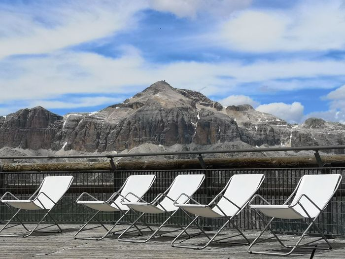 Empty deck  chairs on dolomite mountain against sky