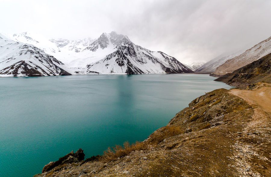 Snow moutains surrounding a lake and a cloudy sky Embalse El Yeso Beauty In Nature Cold Temperature Day Glacier Iceberg Lake Landscape Mountain Mountain Range Nature No People Outdoors Scenics Sky Snow Snowcapped Mountain Tranquil Scene Tranquility Water Weather Winter