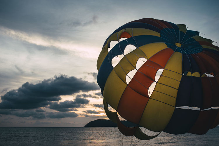 Close-up of parachute by sea against cloudy sky