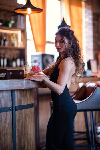Young woman wearing mask at table in cafe