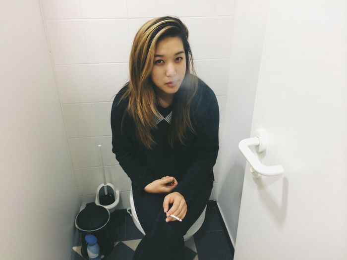 Portrait of woman smoking cigarette while sitting on toilet seat in bathroom