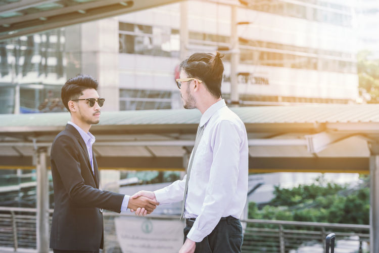 Handshake of Business people Asian  Business City Greeting Happy Japanese  Meeting Agreement Building Business Business Person Businessman Communication Cooperation Coworker Deal Greeting Handshake Men Outdoors Partner Partnership - Teamwork Success Teamwork Young Adult