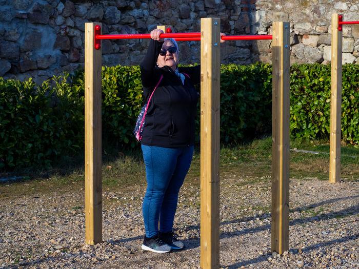 Full length of senior woman exercising at playground