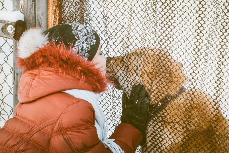 Young woman kissing dog through wire mesh