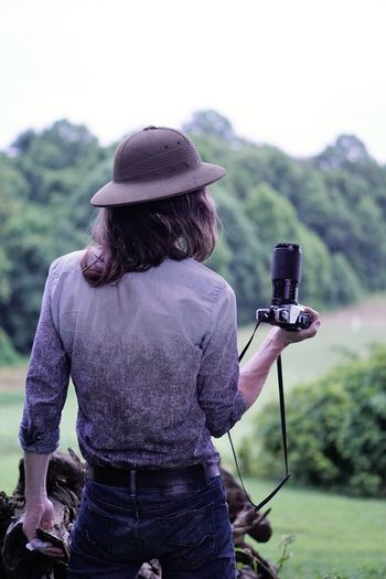 Long-hair model wearing a vintage pith helmet on a nature photography adventure with an old, film canon Adult Field Old-fashioned Pith Helmet Day Focus On Foreground Hairstyle Hat Long Hair Man Model Nature Old Camera One Person Outdoors Photographer Photography Pith Helmet Real People Rear View Safari Standing Vintage Camera