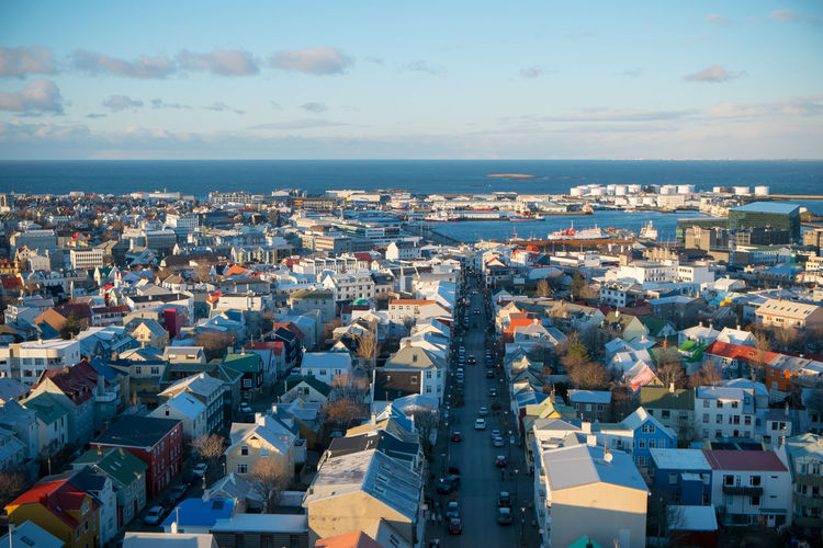 High angle view of town by sea against sky