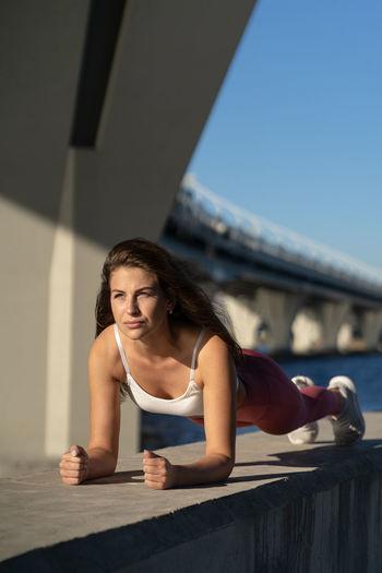 Full length of woman exercising by river against bridge